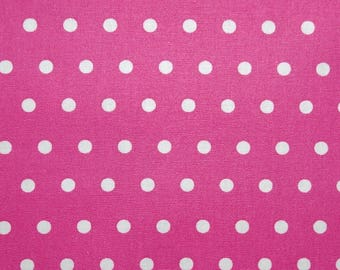 Laminated cotton fabric in fuchsia pink with white polka dots