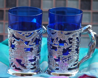 Blue Glass with Silver coloured decorotive cover with women shaped handle.