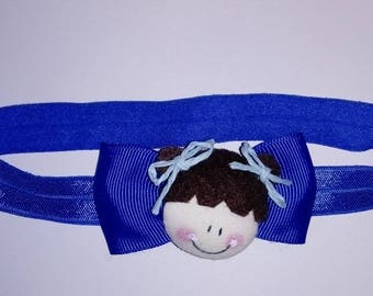 Doll with blue bows. Baby headband