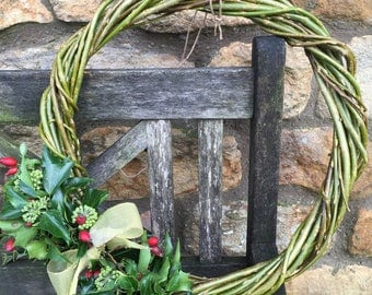 Handmade willow wreath with ornamental greenery and bow