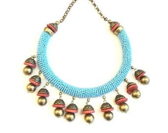Turquoise tribal beads neck piece with a peach and gold jhumka styled dangling.