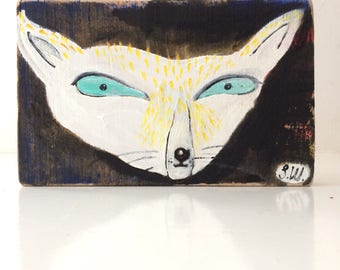 Painting on reclaimed wood of a cat fox creature watching intently .