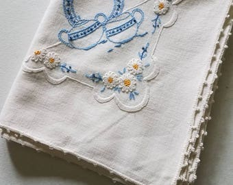 Pretty square tablecloth embroidered in blue and white sugar and creamer motif
