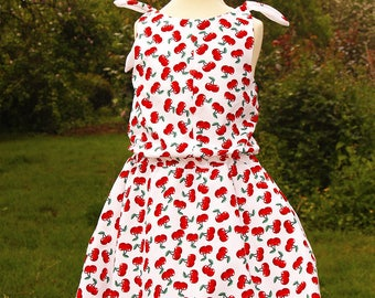 Pin child up in white cotton cherry print dress