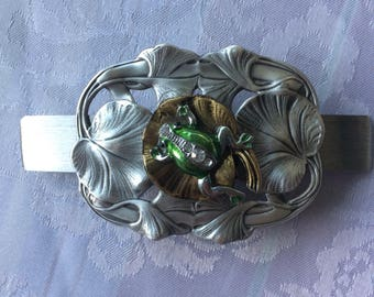 French clip decorated with a sweet green frog on a bed of gold and silver colored lily pads.