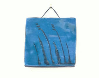 Handmade decorateded tile - blue, with grass decoration.