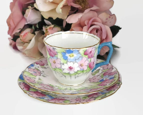 Antique Crown Staffordshire cup, saucer, and plate with pattern of pink and blue flowers, gilt trim, bone china, England, 1906 - 1930