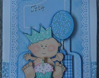 Beautiful handmade baby boy's 1st birthday 3D decoupage card with baby sitting infront of a one with a cupcake in blue.