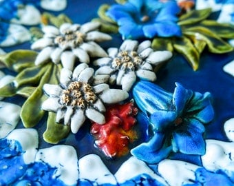 Antique walled volumetric plate made of majolica. Edelweiss, mountain flowers.