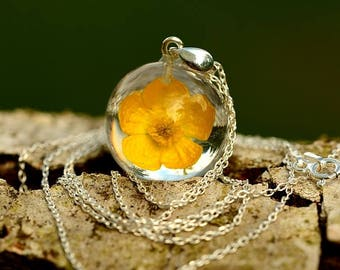 Resin Jewelry. Filigree pendant with real bulbous buttercup (Ranunculus bulbosus) in the resin. Sphere 2 cm. Chain 70 cm.