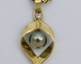 Natural black Tahitian cultured pearl set in 18k hand-fabricated open leaf stylized pendant with .05ct Vs1 diamond