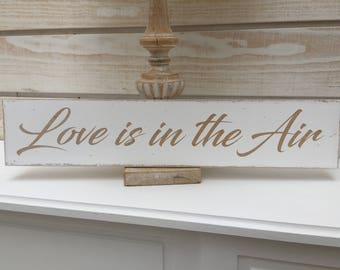 "Weathered wooden sign ""Love is in the Air"""