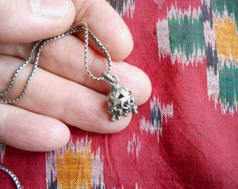 A tiny, delicatly wrought silver bell from India, and narrow sterling chain