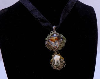 Black lace necklace with flower preserved in resin jewel and racoon tooth on bed of moss