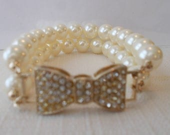 2 Row White Sea Shell Pearl Stretch Cuff Bracelet with a Gold and Clear Rhinestone Bow
