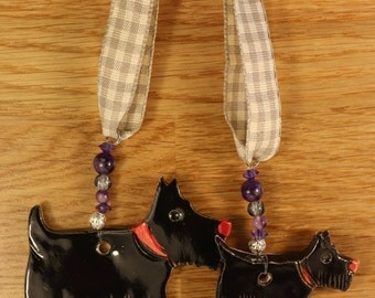Two lovely Black Scottish Terriers Dogs with red collars. Handmade Pottery sent to you in a lovely gossamer bag ready to be given as a gift.