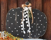 Large black and white pallet pumpkin with white pom and green sprig
