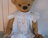 Sweet old English bear in a white lace pinafore, possibly Chad Valley
