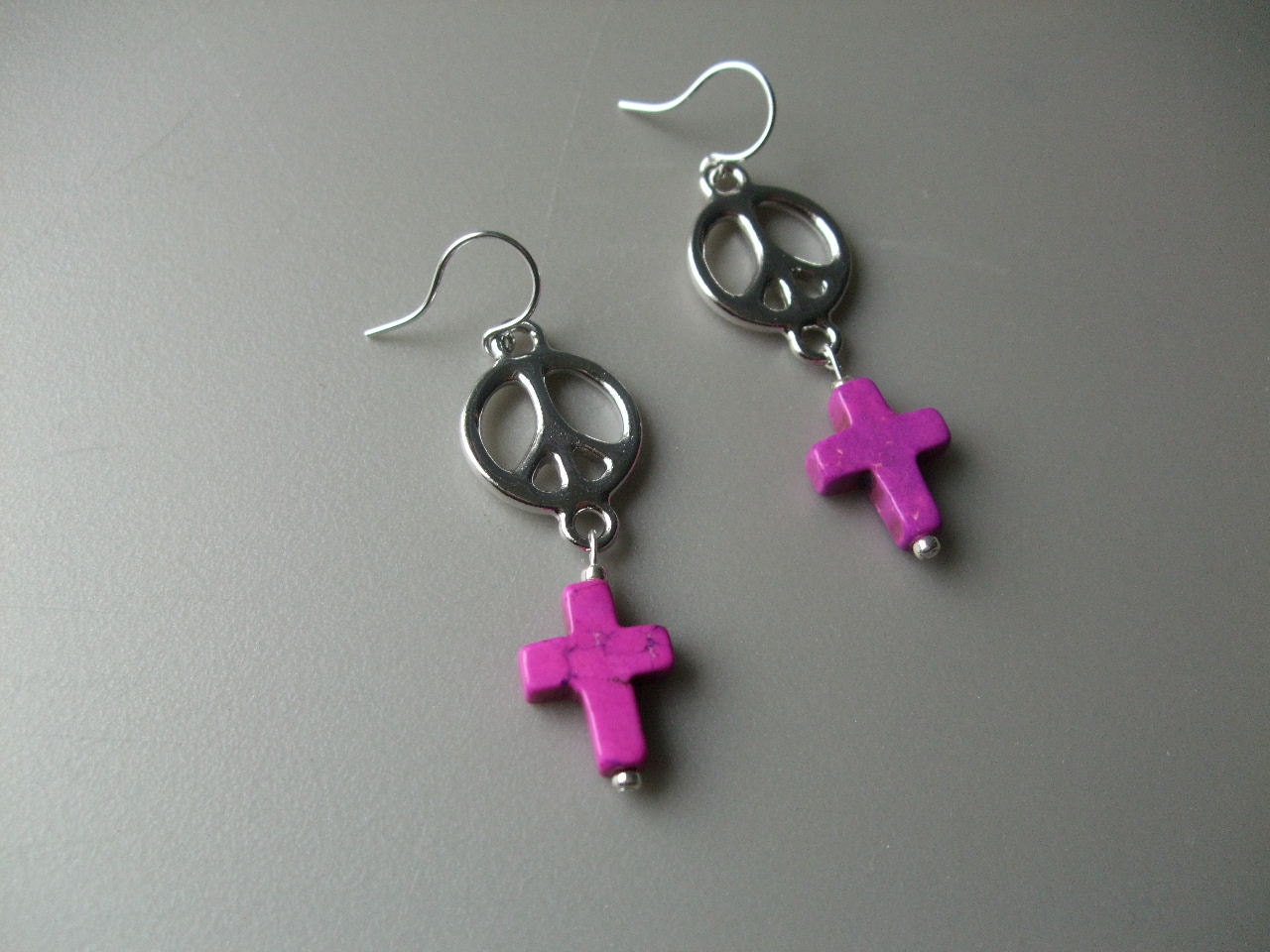 Silver peace sign and purple cross earrings