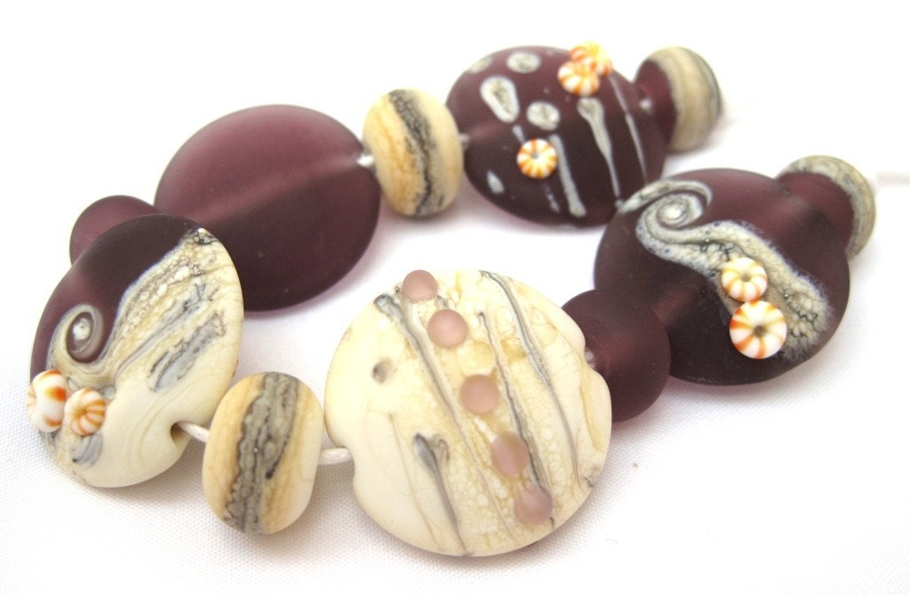 A set of eleven handmade lampwork beads. The set includes five 25mm etched lentils all slightly different and including silvered ivory decoration.