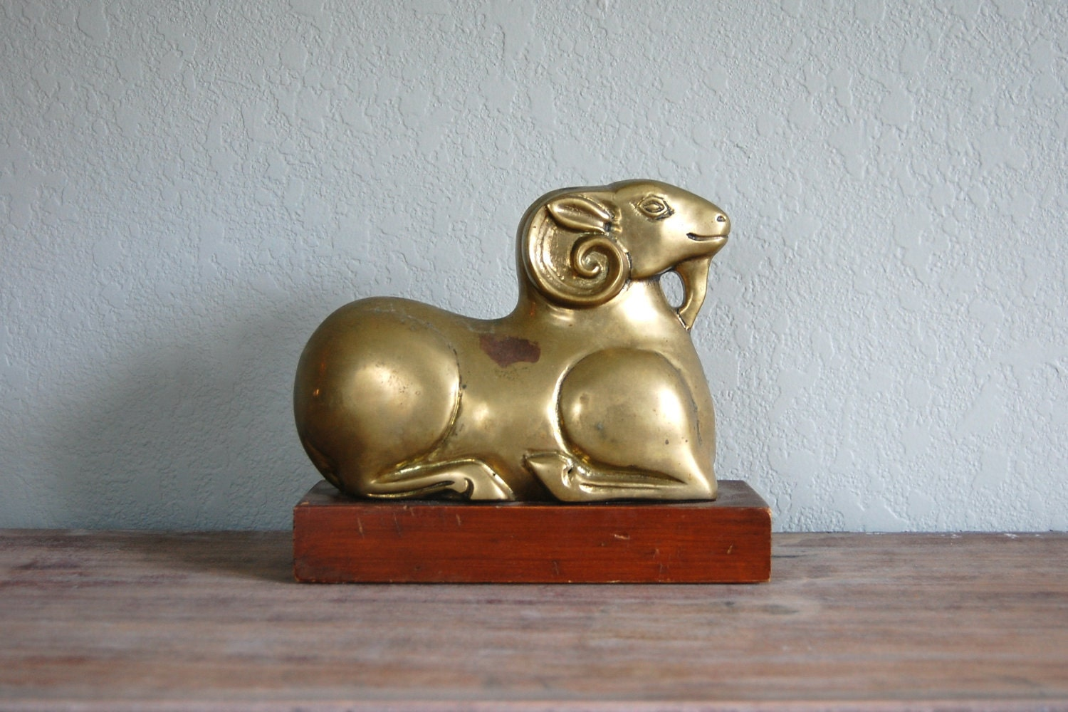 vintage large brass ram on wood