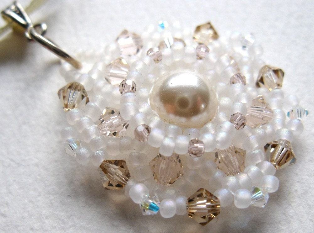 A delicate pendant handwoven from seed beads and crystals, with a glass pearl at its heart.