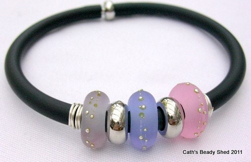 This is a PVC rubber tube bangle with 3 large lampwork glass beads and 2 silver plated spacers.
