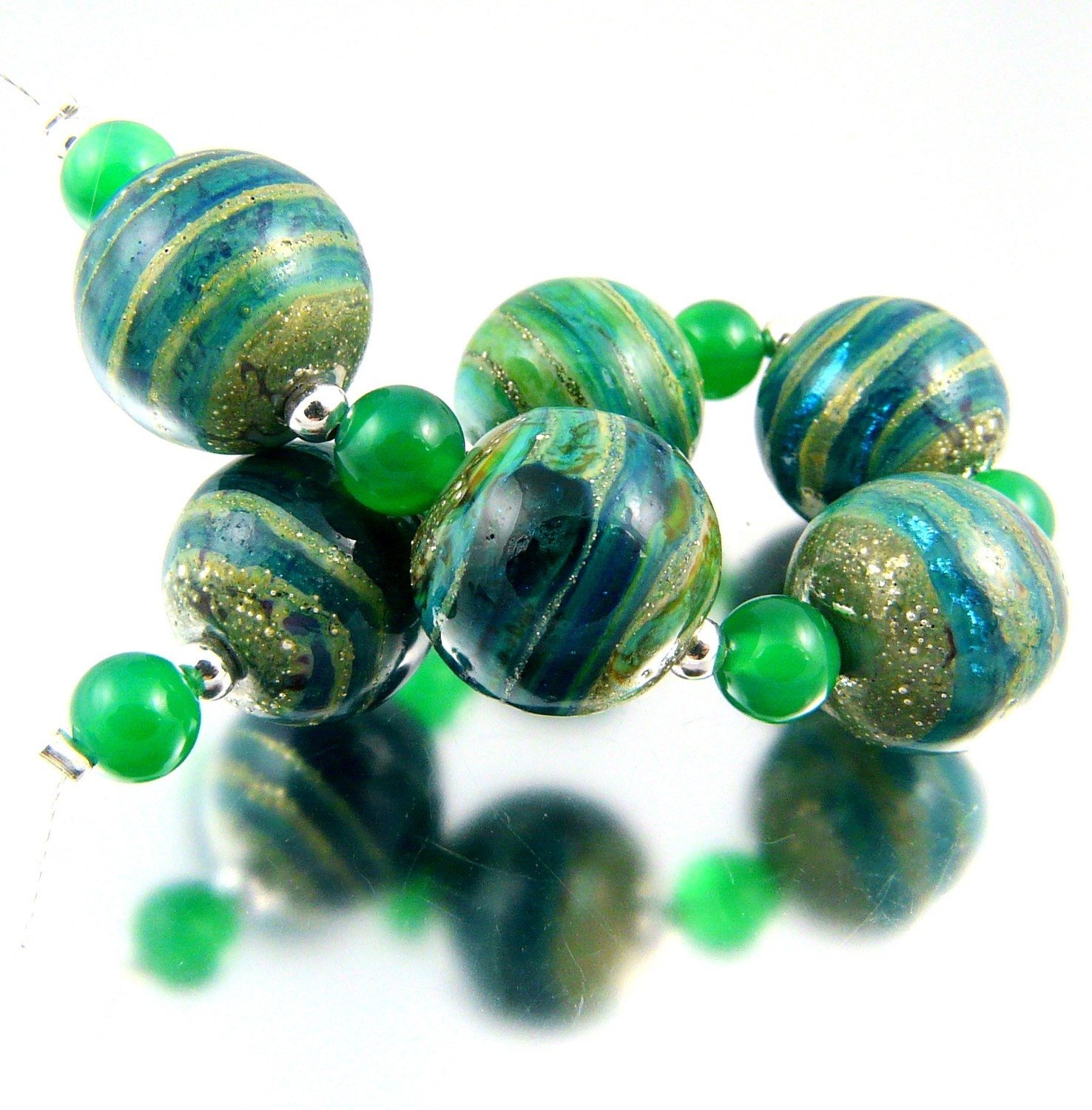 Nigella is a set of 6 handmade lampwork round beads in shades of green and ivory.