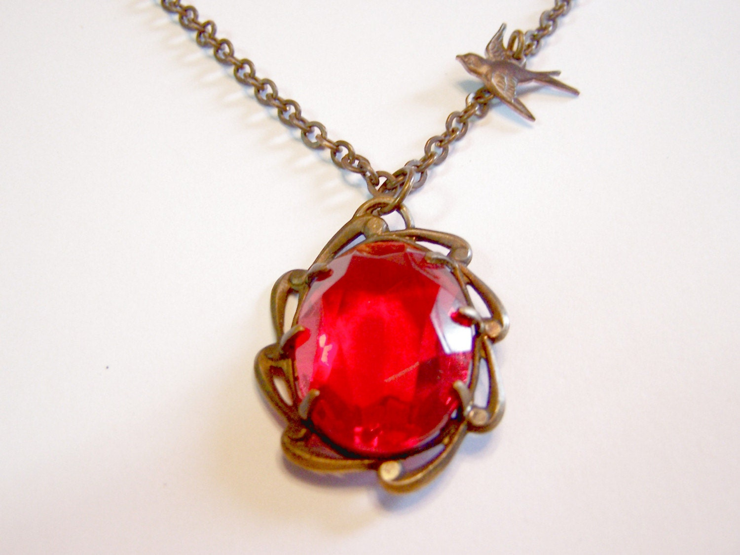 Red Faceted Oval Ruby Glass Stone in Brass Setting with Brass Sparrow Flying High