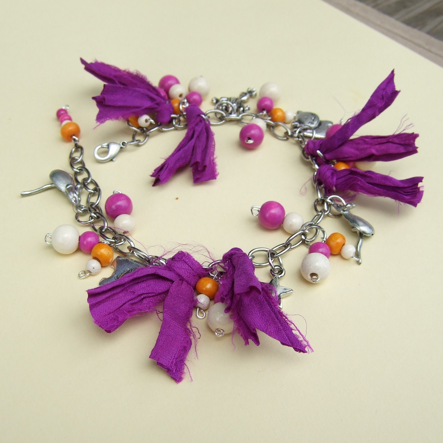 Purple sari ribbon, white, orange and deep pink wood beads, charms and chain bracelet