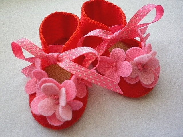 Red baby booties with flamingo pink flowers.