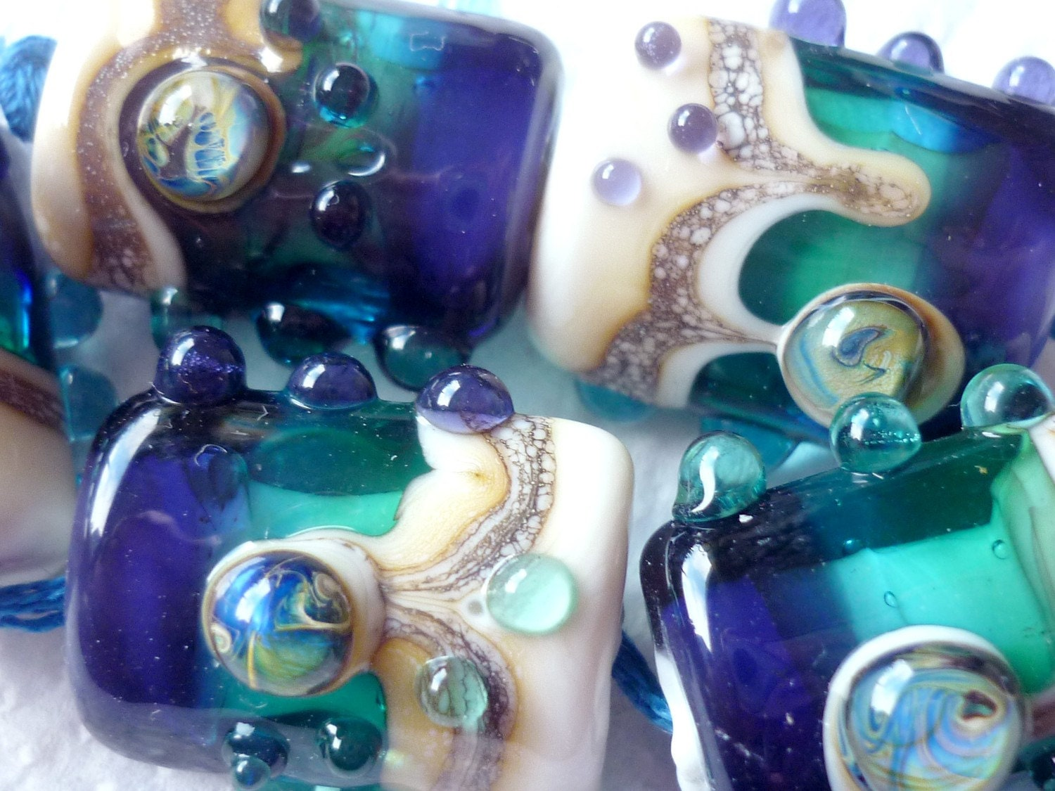 sleek pillow shaped Lampwork Beads made using Pale Ivory Opaque and deep sea blues and greens