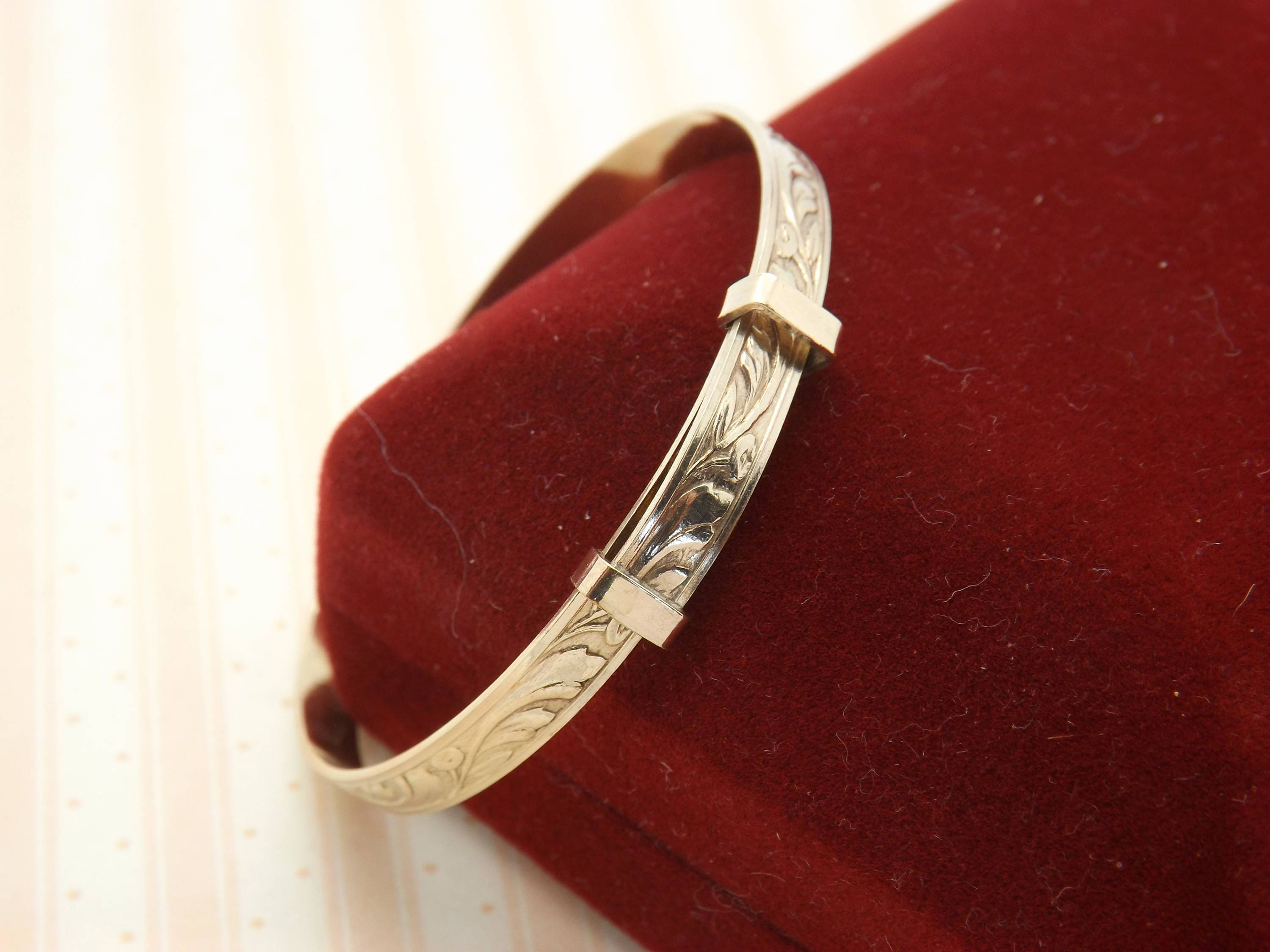 A fine rolled gold childsyoung persons expanding vintage jewelry rolled gold banglebracelet in an engraved floral design.