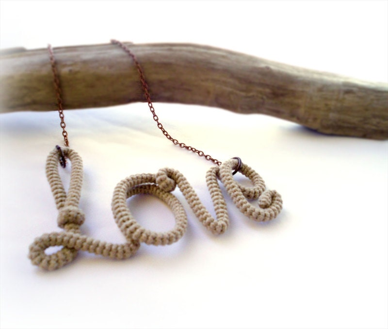 tube yarn necklace spelling the word love in cream