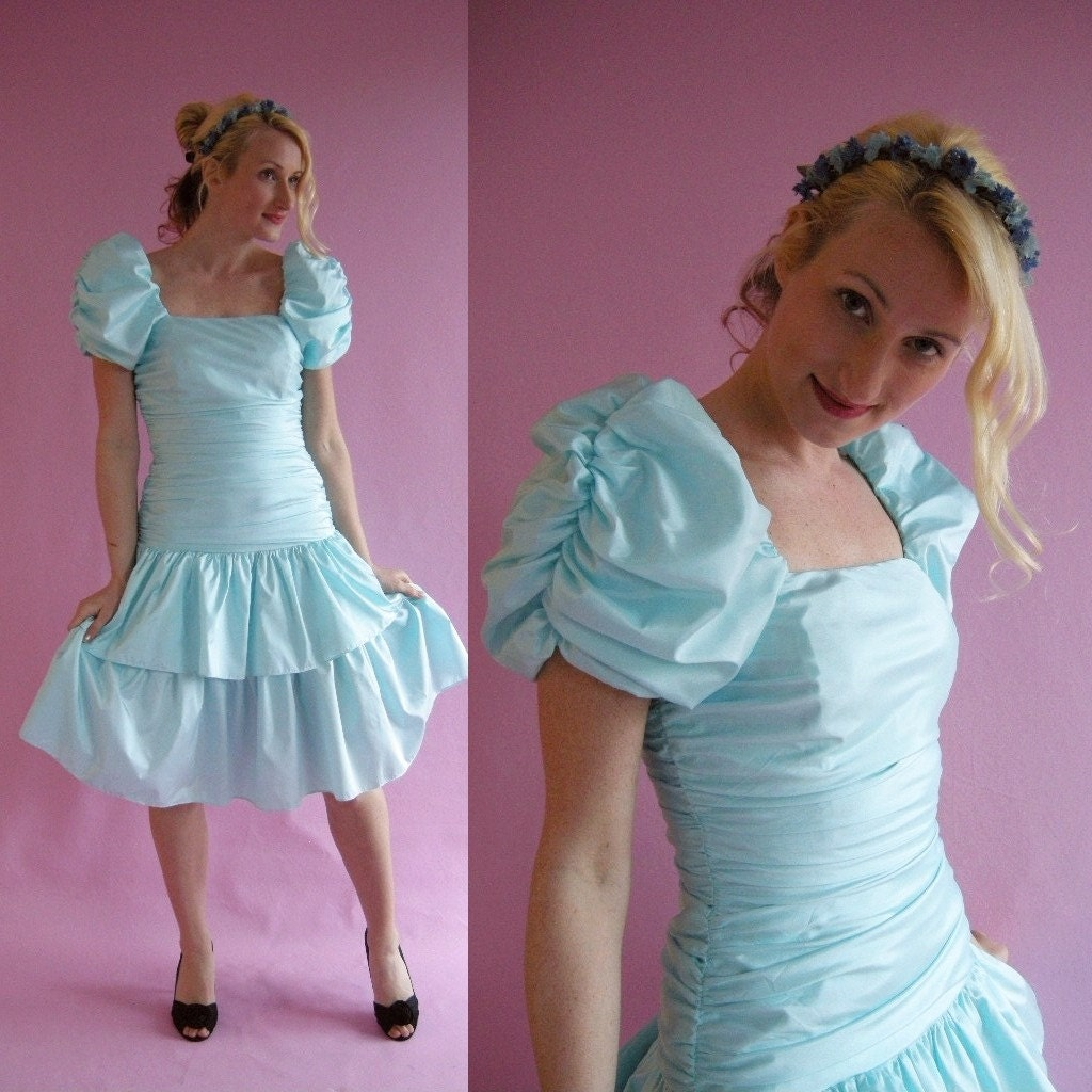 Light blue party dress with puffed sleeves from the 80s. Model is white thin and blonde.