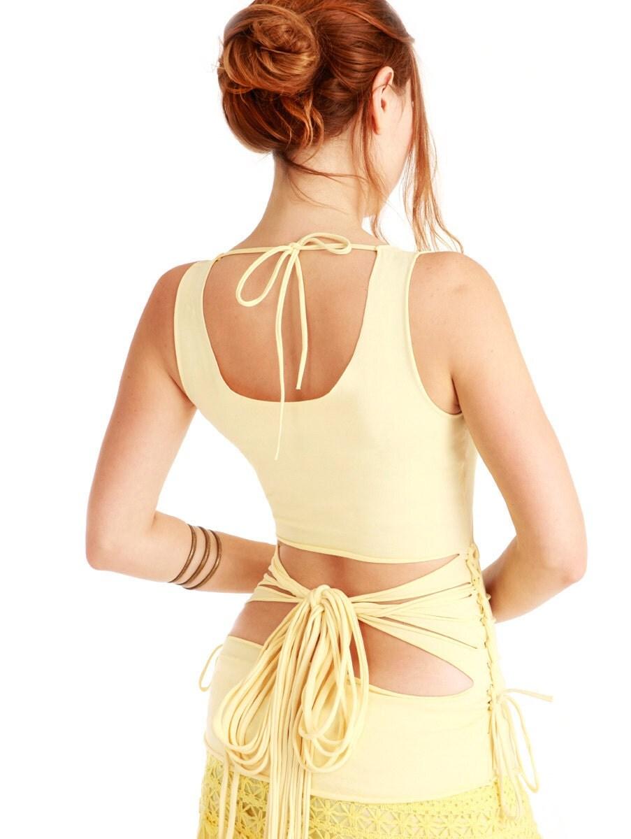 Бледное солнце желтый топ женщины с открытой спиной и щедрым лука