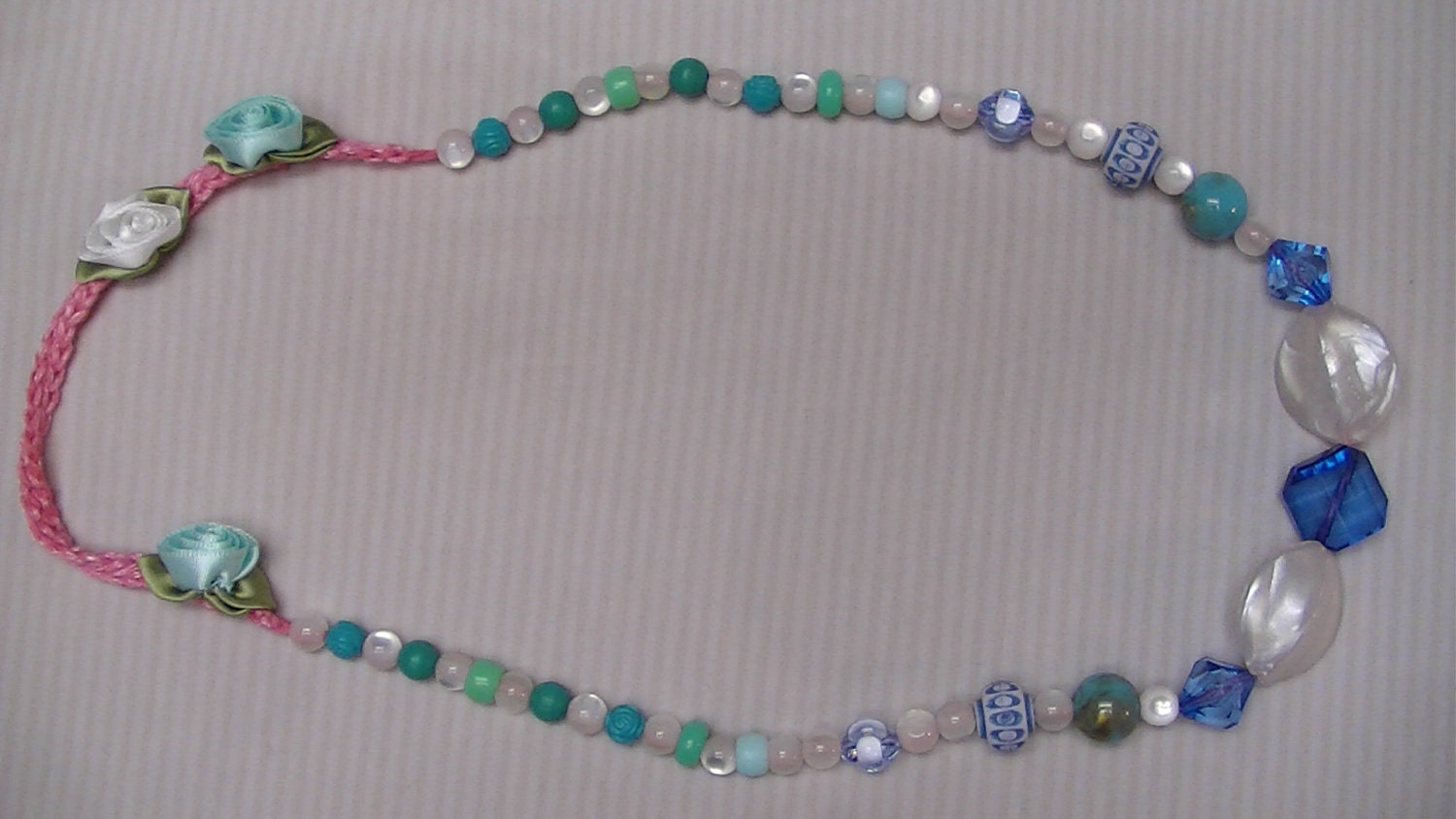 Crochet necklace, ribbon flowers and beads in blue and white.