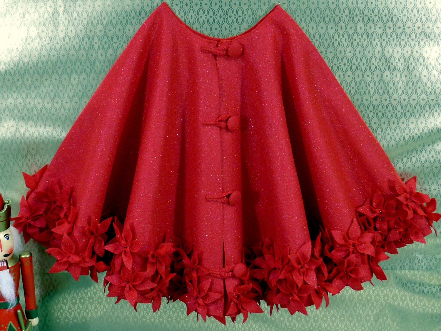 Christmas tree skirt in red glitter felt with hand cut and hand sewn flowers at the hem. 50