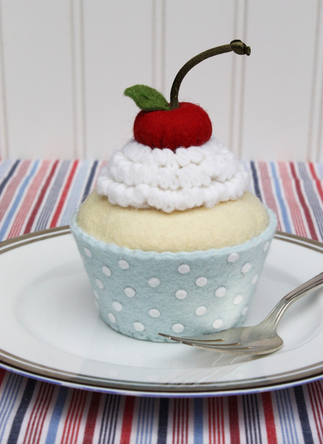 Patriotic Felt Cupcake With White Whipped Cream, Cherry And Blue Liner