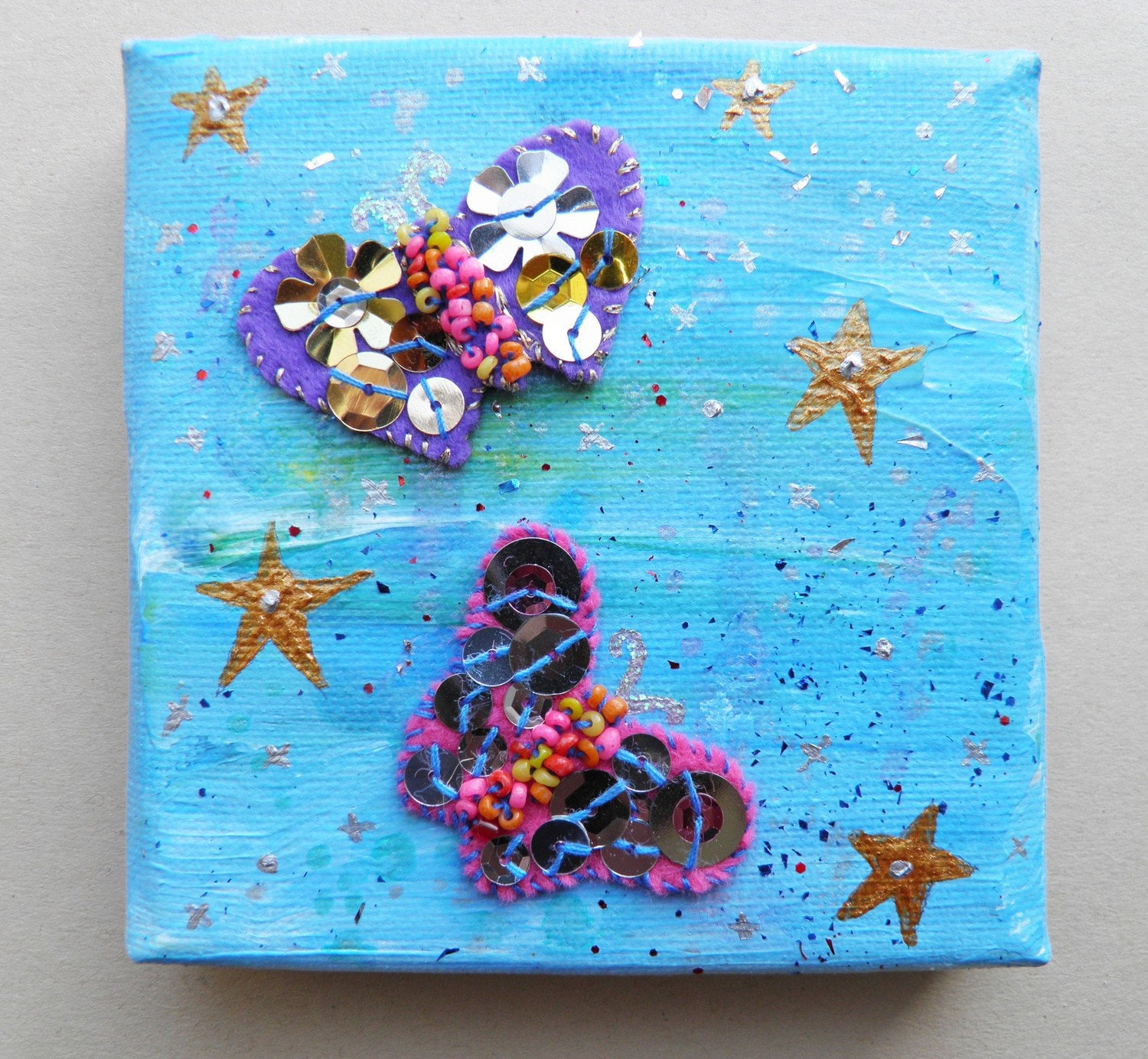 Painted canvas with applique butterflies.