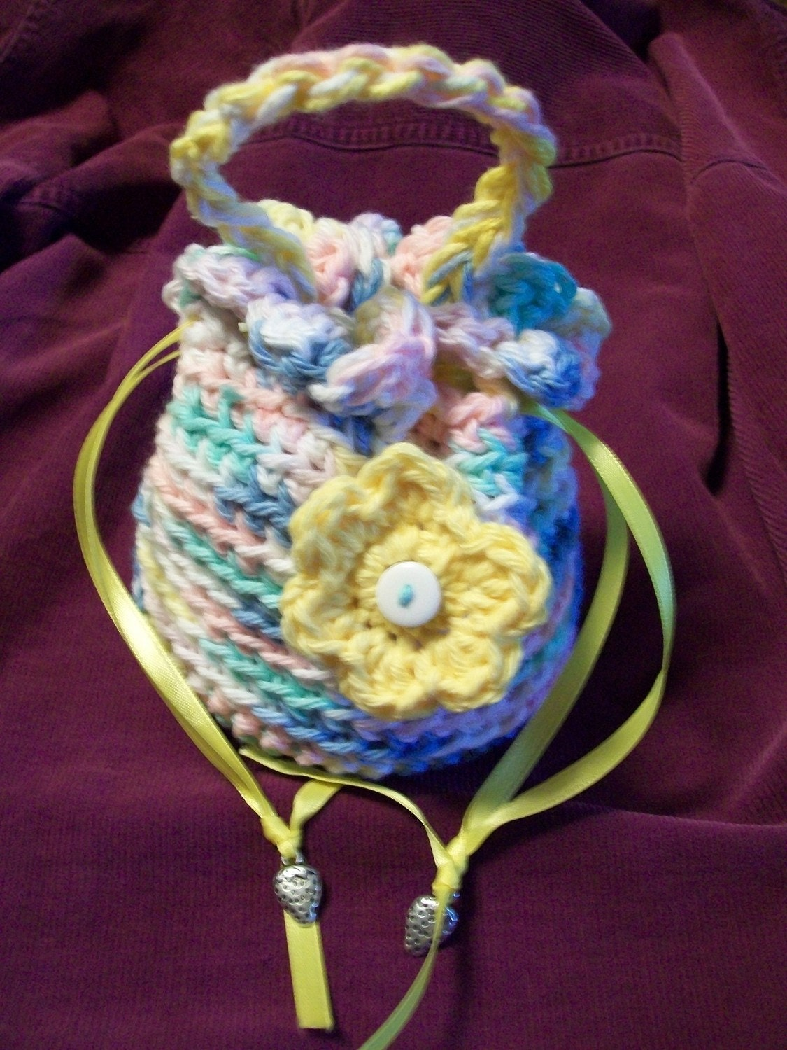 Girl's drawstring crocheted purse in pastel colors with flower.