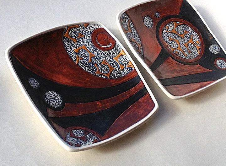 Earthy Red and Black Set of Two Plates with Carved Designs. Pierced foot for hanging. 8.5 X 8.5 Inches. Porcelain. Food & dishwasher safe.