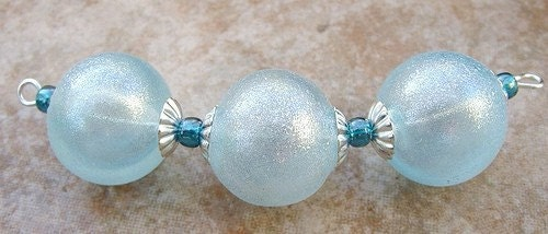 A set of 3 hollow beads in a baby blue shade coated with a subtle shimmer powder.