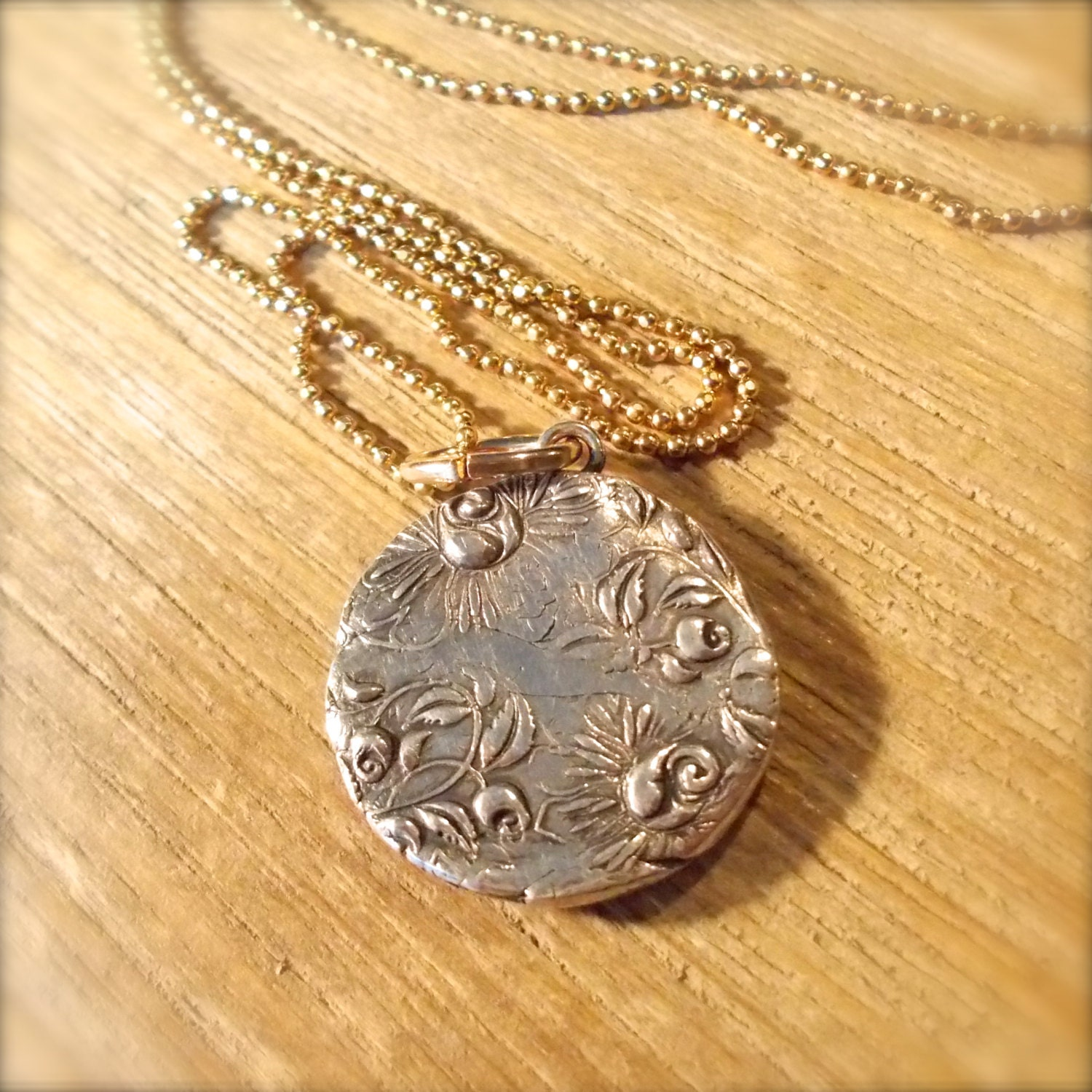 The back of the silver pendant prominently features roses, which in magic signify secrecy and silence.