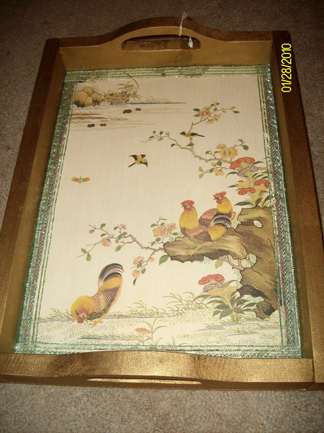 This is a beautiful wooden tray that has been painted gold and then has an oriental printed wallpaper on the bottom with roosters on it.