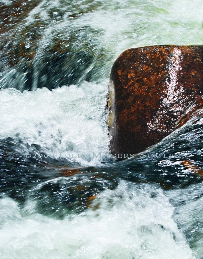 swirling whirlpool with wet boulder in St. Vrain River Rocky Mountain National Park Colorado