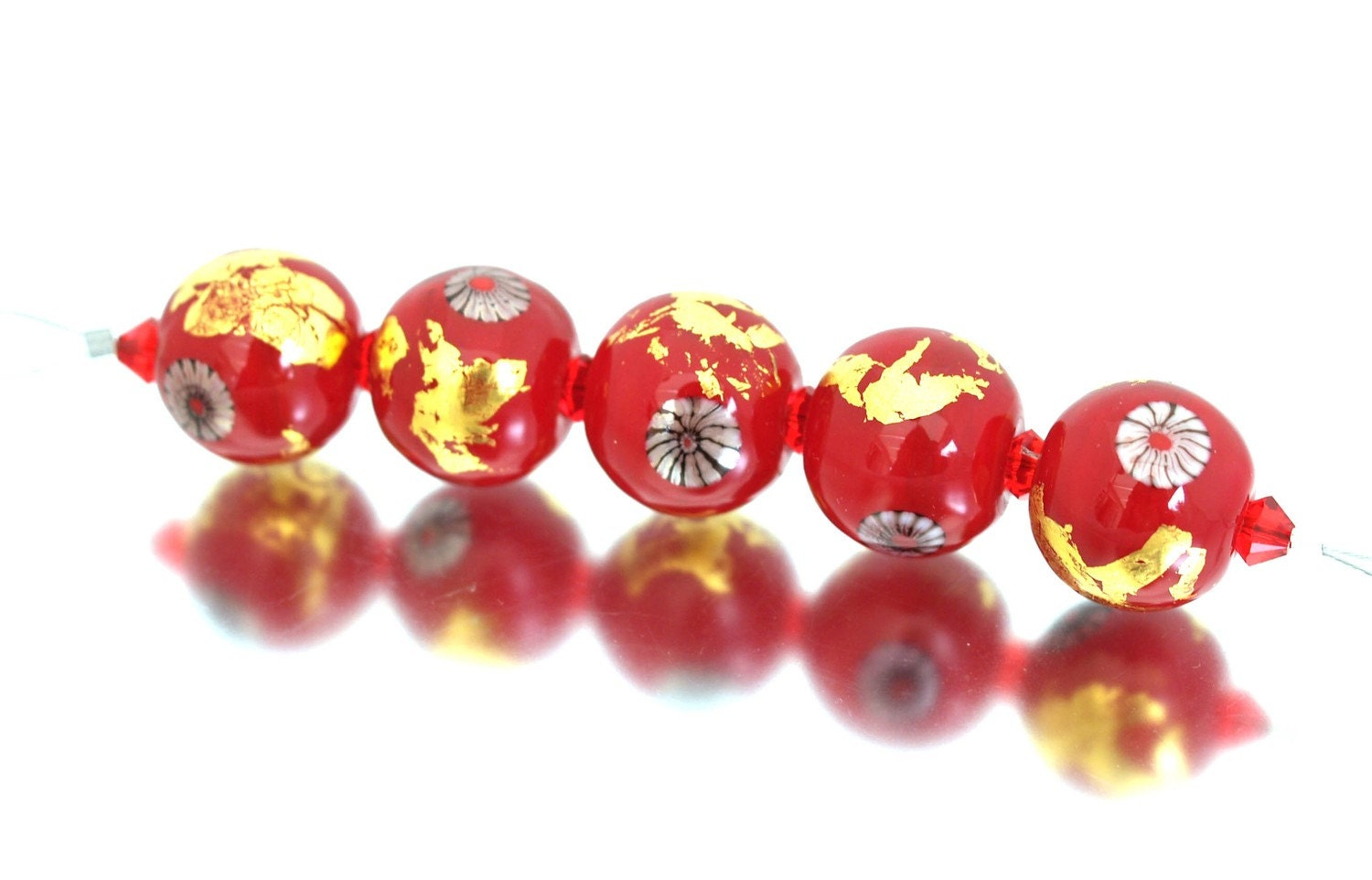 A set of five handmade glass beads in a beautiful scarlet red decorated with gold foil and murrini in black, white and red. This opulent set has an oriental look and would make a stunning piece of jewellery.