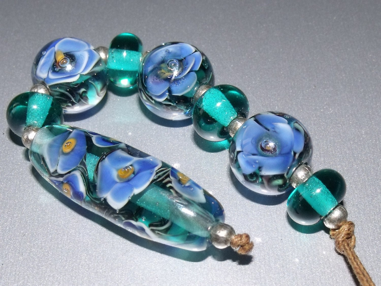 This is a stunning set of florals. They are made on a transparent Teal base, white & blue florals rest upon a varigated vine then they are encased in clear.