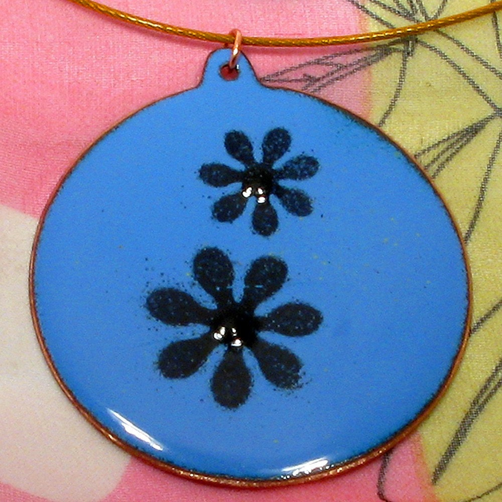 A bright and breezy lavender blue and black enamel on copper pendant with a daisy motif.