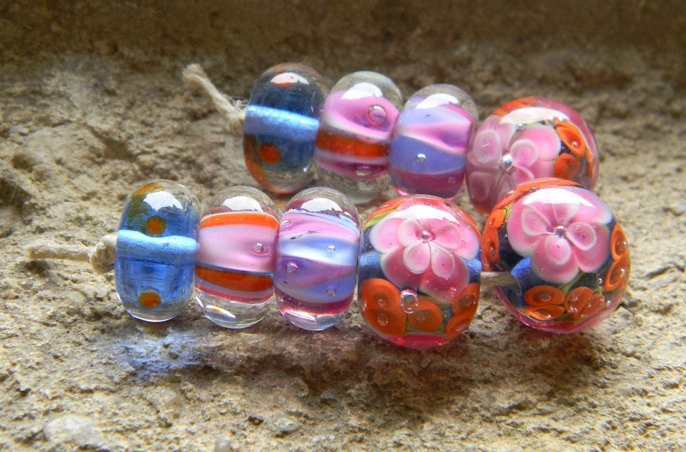 9 beautiful lampwork encased beads, created with clear, pink, coral, white and blue glass.